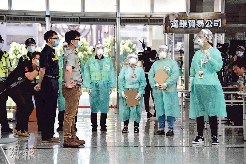 因應新冠肺炎疫情,高雄市政府昨日在四維、鳳山行政中心同步舉辦社區感染防疫實兵演練,參與人員身穿防護衣。(中央社)