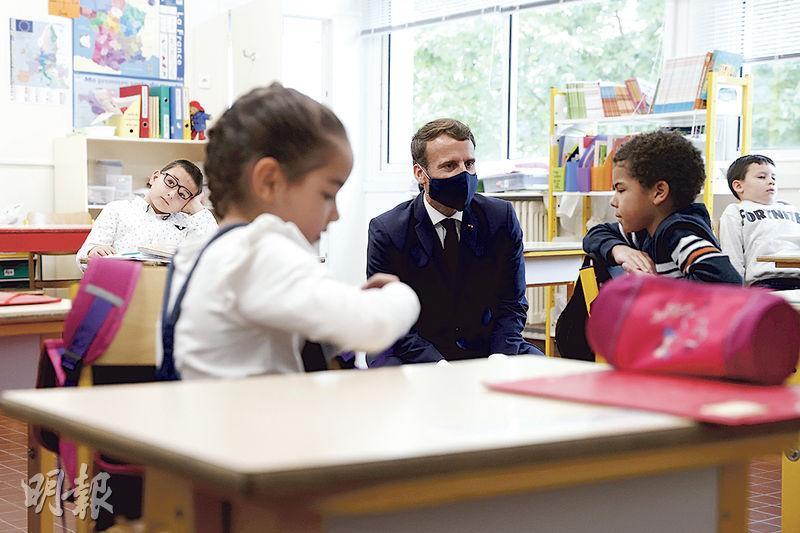法國總統馬克龍(中)昨到普瓦西一所小學探訪,與學童傾談。(法新社)
