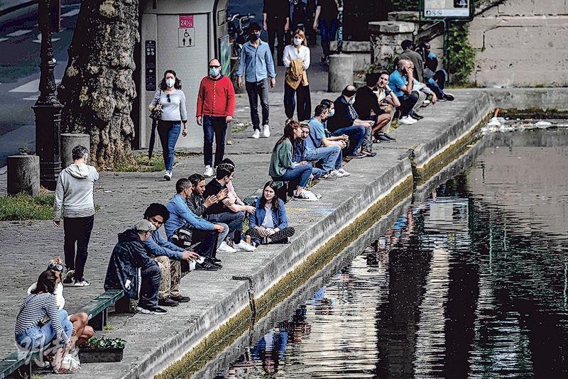 英國擬逐步解除控疫措施,而鄰國法國亦預計本周逐步解封。圖為首都巴黎的市民到聖馬丁運河河畔歇息。(法新社)