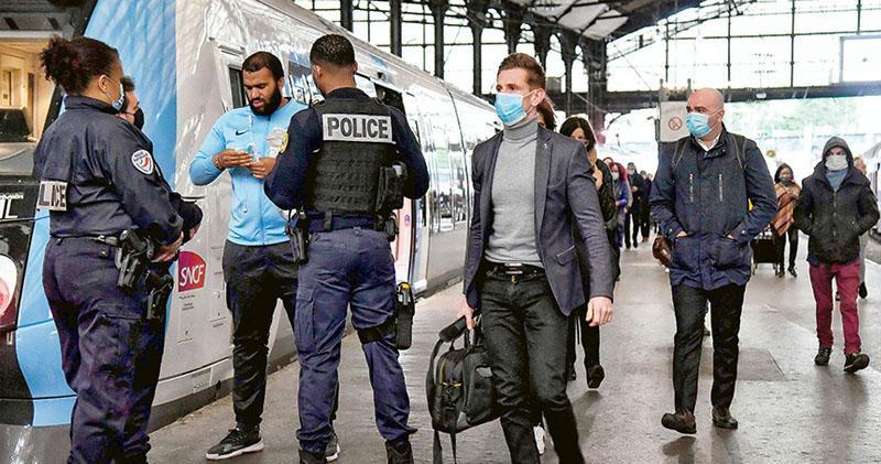 5月11日法國放寬控疫限制首日,警員在巴黎聖拉扎爾火車站檢查及要求乘客戴口罩。法國官方要求所有公共交通工具乘客均須戴口罩。(法新社)