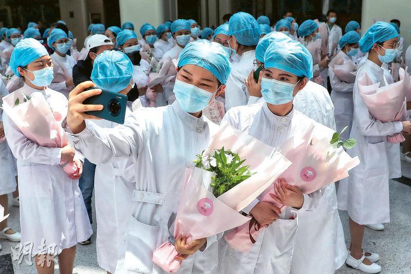 昨日是國際護士節,經歷了殘酷的新冠疫情之後,內地今年的主題是「致敬護士隊伍,攜手戰勝疫情」。在武漢同濟醫院,發布護理抗疫歷程記事視頻,並表彰在此次疫情中表現突出的個人與團體。其中百餘名不同年代出生的老中青護士代表,一起重溫南丁格爾誓辭,迎接這個特殊的節日。有獲贈鮮花的護士,開心地捧着鮮花自拍。(路透社)