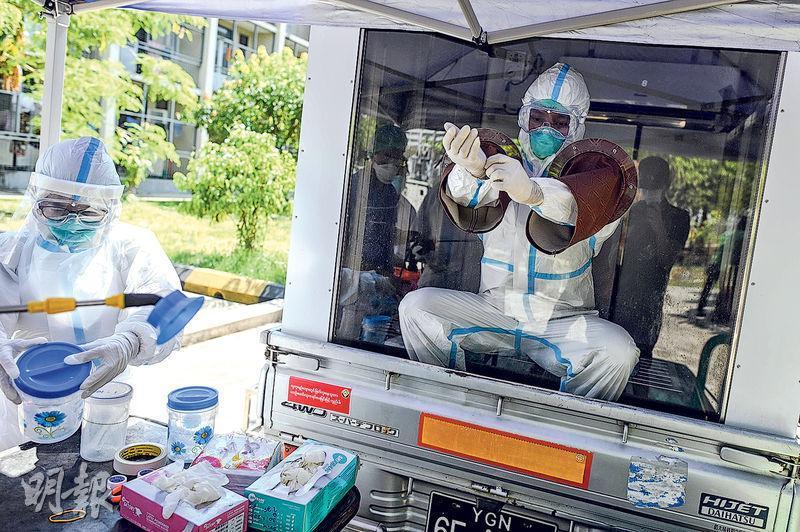 緬甸全副裝備的醫護人員昨在仰光檢疫中心清洗保護衣物。(法新社)