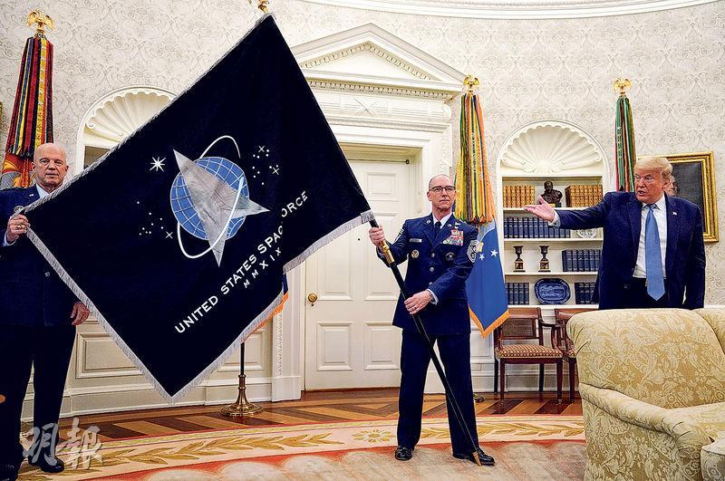 美國總統特朗普上周五在白宮橢圓形辦公室內,介紹太空部隊旗幟(圖)及宣稱正研製比現有導彈快17倍的「超勁導彈」。 (路透社)