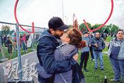 於德國和瑞士兩地相思多個星期的盧卡斯和萊奧妮,上周五一待封關的圍網拆走,即在邊境擁吻。(路透社)