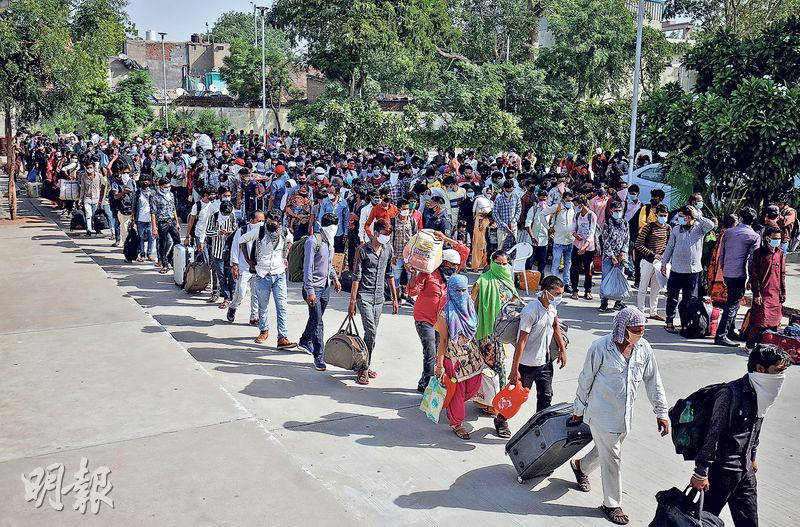 印度鐵路停駛7周後,昨局部復通,大批滯留外地的勞工排隊搭車往鐵路站返鄉。(路透社)