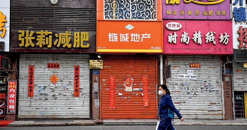 內地今年上半年大多數時間都集中於抗疫,經濟活動幾陷停滯,今年兩會制定經濟增長(GDP)目標的水平高低,甚至乎會否制定,將代表中央對疫後振經濟的態度與信心。圖為市民昨日從吉林市豐滿區因疫情關閉的商舖前經過。(新華社)
