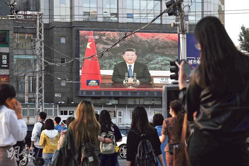 一年一度的世衛大會昨天以視像形式開幕,國家主席習近平受邀致辭。圖為北京一個戶外巨型電子屏幕正在播放有關習近平致辭的新聞。(法新社)