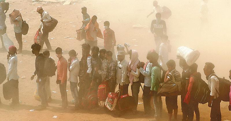 印度為遏新冠疫情擴散,自3月底已全國封城近7周。大量離家打工的民工在停工之下被迫暫時返鄉,但由於全國列車只有限度服務,令各地滯留民工遲遲未能疏散。圖為有民工周一冒着沙塵,在新德里市郊輪候搭巴士準備返回東部比哈爾邦的故鄉。(路透社)
