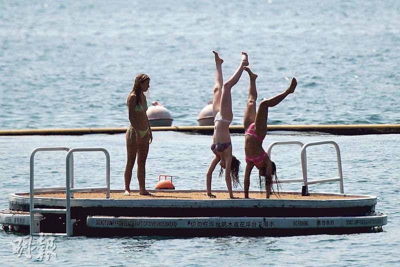 康文署轄下15個公衆泳灘本周六重新開放,當中包括淺水灣。雖然淺水灣泳灘暫停了救生服務,昨午仍有不少泳客暢泳,更有人游到浮台做倒豎葱。(楊柏賢攝)