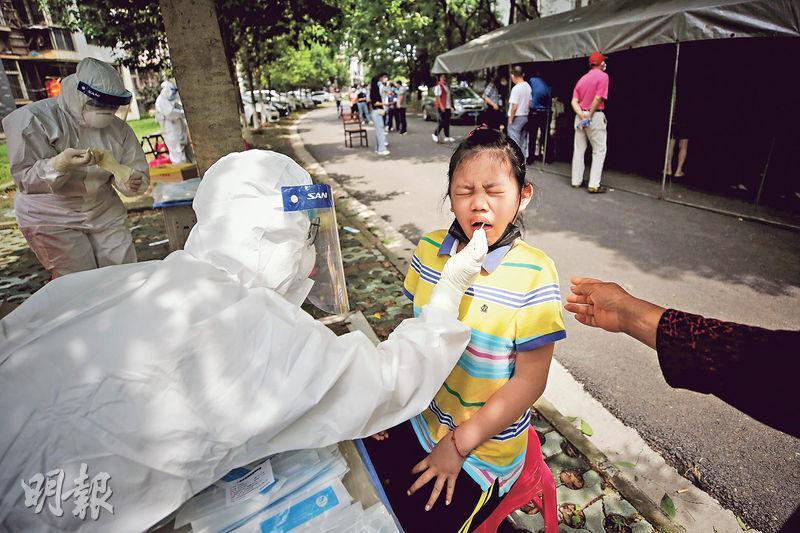 在武漢,有母親在女兒感染新冠病毒離世後,追究瞞疫官員的法律責任及反人類行為。也有人代委員稱要在兩會建議修改《傳染病防治法》,讓地方官員有公布疫情及預警的權力。圖為近日武漢出現多宗確診個案,當局進行全面核酸檢測,16日有醫務人員對小童採樣。(法新社)