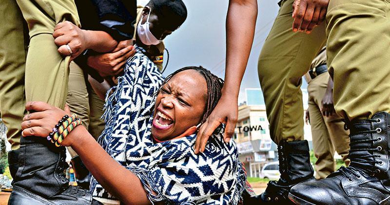 非洲國家烏干達警方周一(18日)拘捕抗議封城令的著名學者尼安齊(Stella Nyanzi,中),指控她涉嫌煽動暴力。該國現時下令關閉學校及暫停商業活動,禁止舉行公眾聚會,除了醫護人員等從事必要行業的勞工外亦不可使用私人或公共車輛,被視為非洲最嚴厲的封城措施之一。尼安齊在首都坎帕拉被捕之際,正和其他社運人士嘗試向總理遞交請願書,要求政府取消封城令、向民眾免費派發口罩,並釋放數以千計被指違反抗疫措施的人。她近年因公開批評總統穆塞韋尼(Yoweri Museveni)打壓異見人士和執政長達數十年,而在社交網絡備受關注。(路透社)