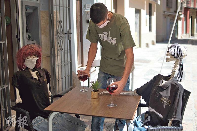 西班牙開始逐步解除封城,南部馬拉加有酒吧將骷髏骨模型打扮成客人的樣子,侍應把兩杯酒送到枱上。(法新社)