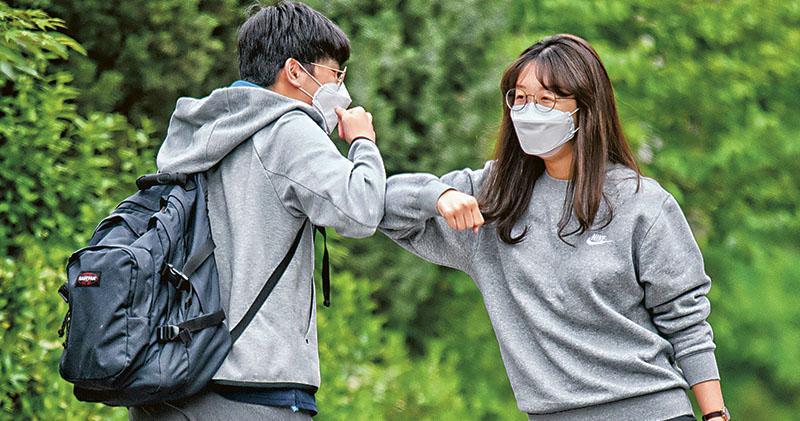 韓國學校受疫情影響延遲逾兩個月開學,因應疫情近日有放緩迹象,當地學校昨開始分階段復課。在首爾,老牌學校景福高等學校的學生昨日亦重返校園,一名女職員(右)與學生碰肘打招呼。(法新社)