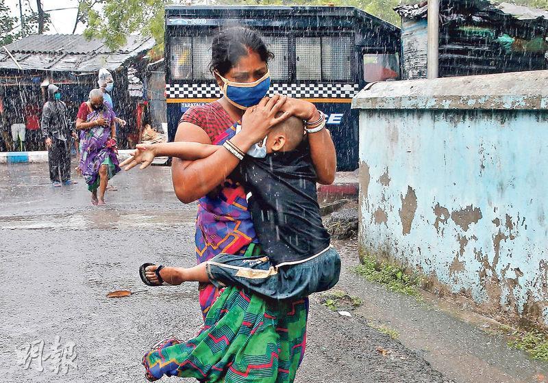 在印度加爾各答,昨日有婦女懷抱幼兒冒雨疏散,以避風暴來襲。(路透社)