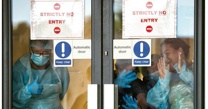 英國利物浦安特里大學醫院的醫護人員周四隔着嚴限出入的玻璃門,回應為國民保健服務(NHS)職工打氣行動。英國政府將為醫護等做抗體測試,據以發出「免疫護照」,方便社會區分哪類人較可能低感染及傳播冠狀病毒風險。(路透社)