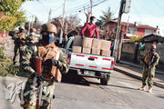 世衛稱南美洲已成疫情「新震央」,反映區內控疫成果不佳。圖為智利首都聖地亞哥市郊的金塔諾馬爾,有士兵上周五護送運載食物包裹的卡車。(路透社)