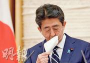 日本首相安倍晉三昨在記者會宣布全國解除新冠病毒緊急事態前,先除下口罩。(法新社)