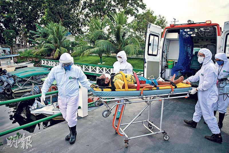 巴西的新冠疫情仍然嚴重,帕拉州的醫護人員不敢怠慢,周一穿著防護服用擔架把一名感染者送上救護車。(法新社)
