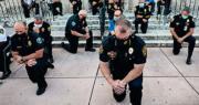 佛羅里達州科勒爾蓋布爾斯市一批來自不同警察部門的警員,上周六在一場哀悼弗洛伊德遇害、促停警暴的集會上以單膝跪着,與示威者一同祈禱。美式足球員卡佩尼克2016年起在賽場單膝「跪國歌」抗議警察欺壓黑人和種族歧視,其後單膝跪成為抗爭象徵。(法新社)