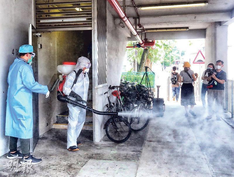 昨早有穿上保護衣的人員為祿泉樓及周圍消毒,噴上化學物。(李紹昌攝)