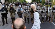 美國憲兵隊員(後)周一在白宮外戒備,面對舉起拳頭抗議種族主義和警暴的示威者。(法新社)