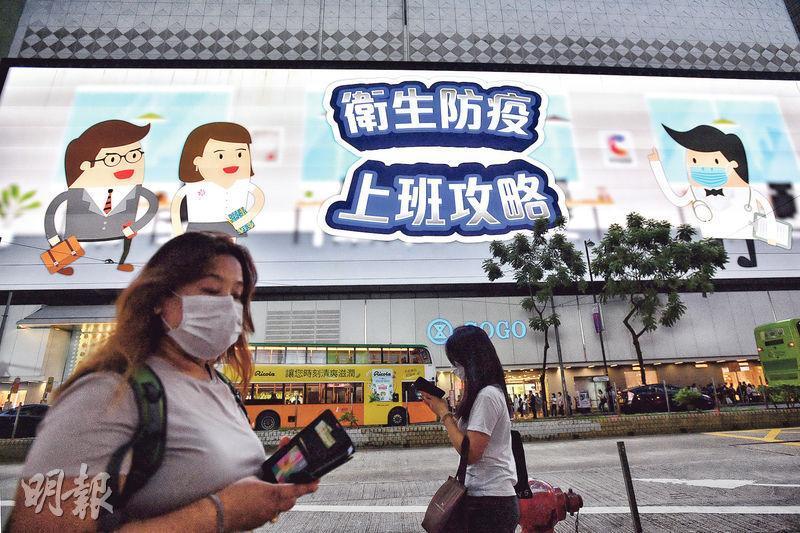 近日本港再出現本地感染個案,沙田瀝源邨更爆發群組感染,銅鑼灣崇光百貨外的大型廣告屏播放廣告,提醒市民防疫。(鄧宗弘攝)