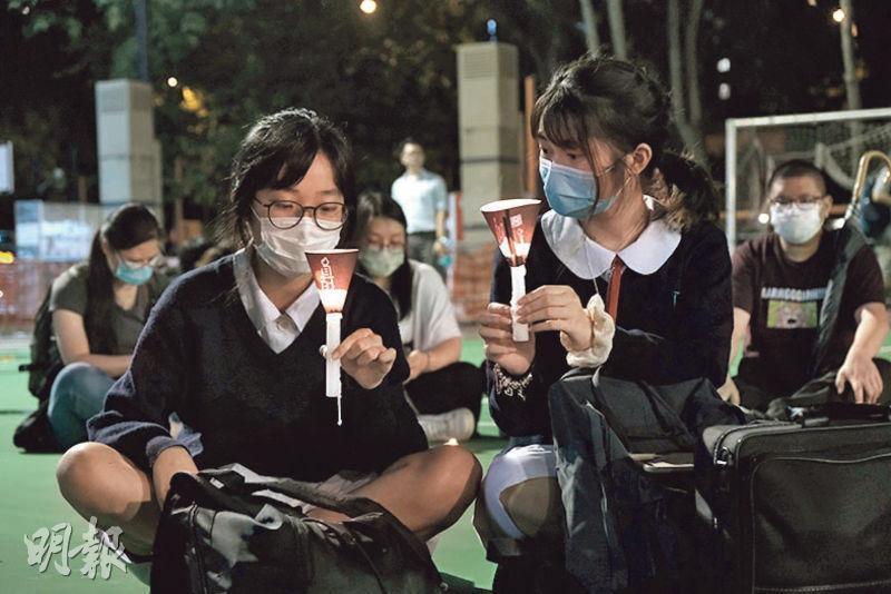 中學生Brittany(右)和Claire(左)首次出席六四悼念活動,她們遮蓋校徽免被識穿身分。Claire說選擇到維園是對香港傳統的傳承,Brittany說去年開始覺得反修例運動與六四有連結。(馮凱鍵攝)
