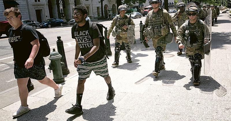 首都華盛頓街頭,周四有美軍前往站崗途中,跟示威者一起在街上走過。(法新社)