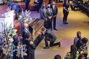美國黑人男子弗洛伊德之死觸發全國反種族主義和反警暴示威浪潮,其追悼會周四在明尼阿波利斯市舉行,一名男子在他靈柩前單膝跪下致哀。(路透社)