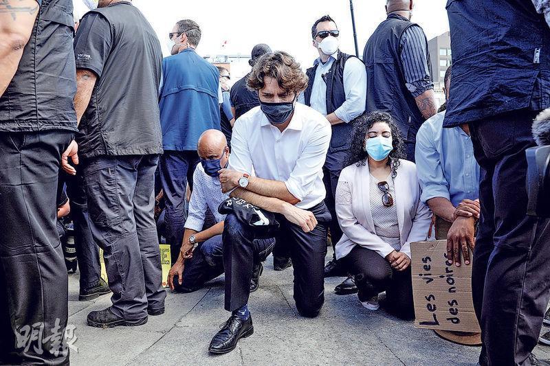 加拿大總理杜魯多(中)上周五出席在渥太華國會山莊舉行的集會,聲援美國反種族歧視和反警暴示威,其間戴着口罩的他單膝跪地。(路透社)