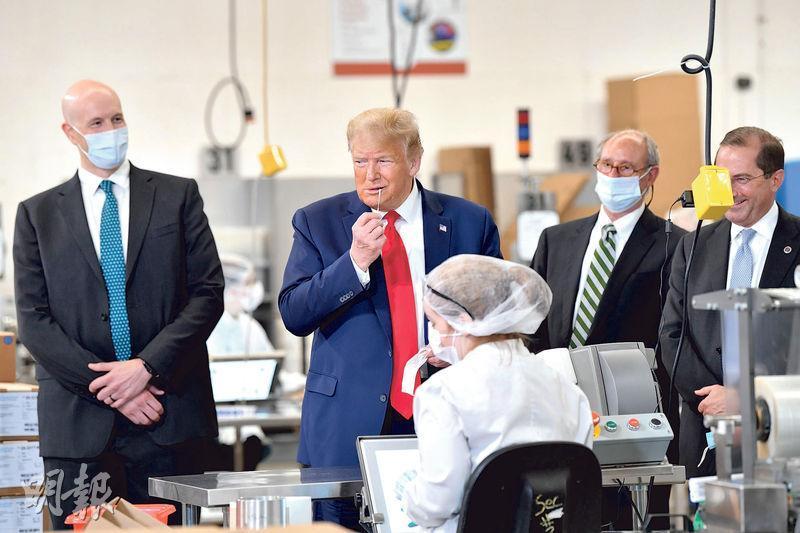 美國總統特朗普上周五(5日)參觀緬因州普里坦醫療用品廠房,其間假裝用鼻腔試棒做測試。(法新社)