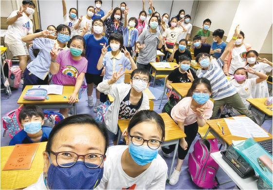 香港培道小學一眾小五生闊別校園多月,昨穿便服回校上課,心情興奮,他們與教師及校長陳敏儀(前排左)自拍留影。(學校提供)