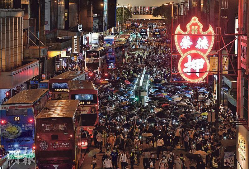 昨日是去年6月9日「百萬人上街」反修例遊行一周年,大批市民昨晚在中環遊行,並走出馬路,其間不少人亮起手提電話的燈光,亦有人撐起雨傘,沿途大叫「光復香港,時代革命」等口號。(鄧宗弘攝)