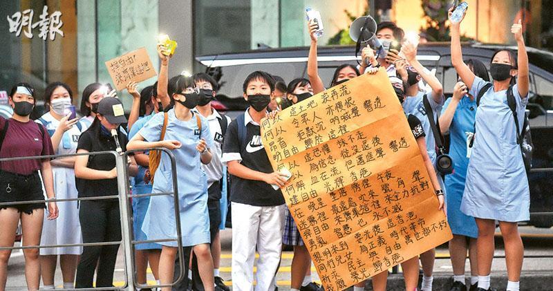 反修例風波下,《願榮光歸香港》歌聲不時響起,圖為去年9月,有學生在九龍塘達之路拉人鏈,有人展示《願榮光歸香港》歌詞。(資料圖片)