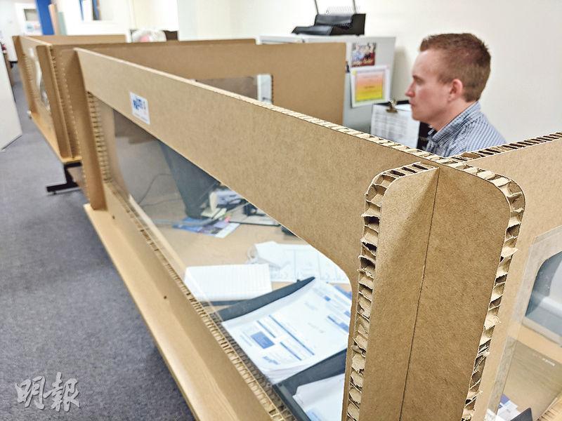 英國包裝公司Pallite近日利用紙皮和透明膠片作材料,設計製造出供辦公室使用的枱面間隔,方便打工一族保持社交距離。(路透社)
