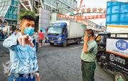 北京昨日確診新冠肺炎的中國肉類食品綜合研究中心兩名人員,曾到京深海鮮市場採集樣本。目前京深海鮮市場已經封閉消毒,有戴着口罩的保安人員在入口處阻止無關人等入內。(路透社)