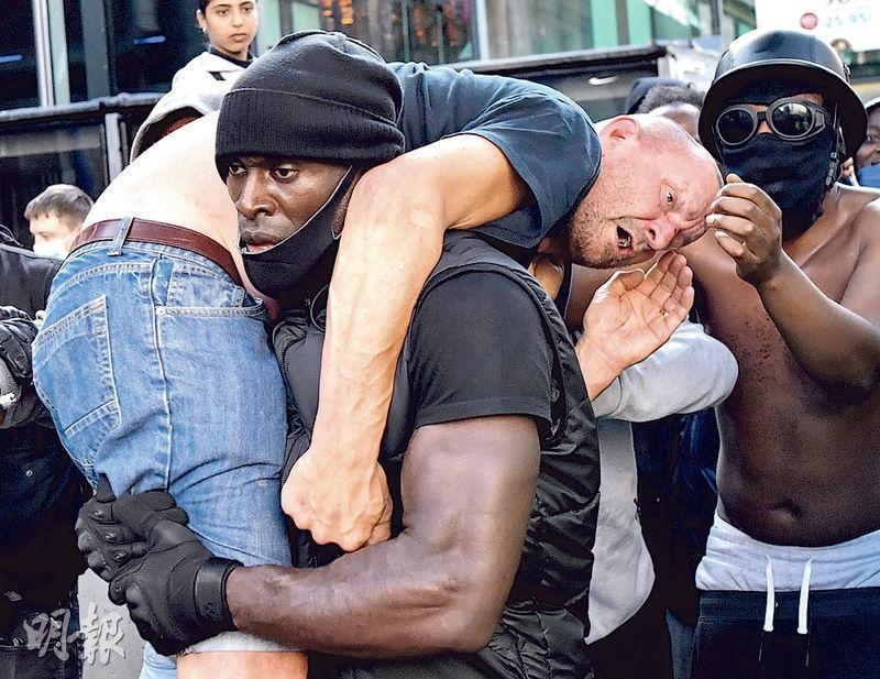 倫敦前天有「黑人的命也是命」示威,數名黑人男子把一名受傷的打對台白人示威者抱到安全地方。(路透社)