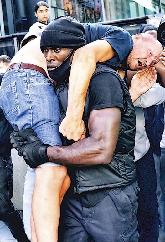 英國黑人哈欽森與另外4名「大隻佬」友人組成救人小組,原意是想在「黑人的命也是命」等示威現場保護年輕的示威者免受傷害。哈欽森上周六在倫敦示威現場扛着一名受傷的極右白人示威者到安全地方(圖),受外界讚揚是「英雄」。(路透社)