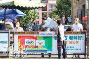 本月11日起出現新一輪疫情的北京西城區,多個小區已經封閉,昨日快遞員也不能入內,要收件者隔着鐵閘領件。(明報記者攝)