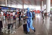 北京再爆發新型冠狀病毒,大量航班取消,而到北京首都國際機場的人則做足防疫措施戴上口罩,更有人穿全身保護衣。(路透社)