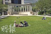美國芝加哥周一有民眾在當地的千禧公園休憩時遵守社交距離措施,坐在草地上畫設的圈內。(法新社)