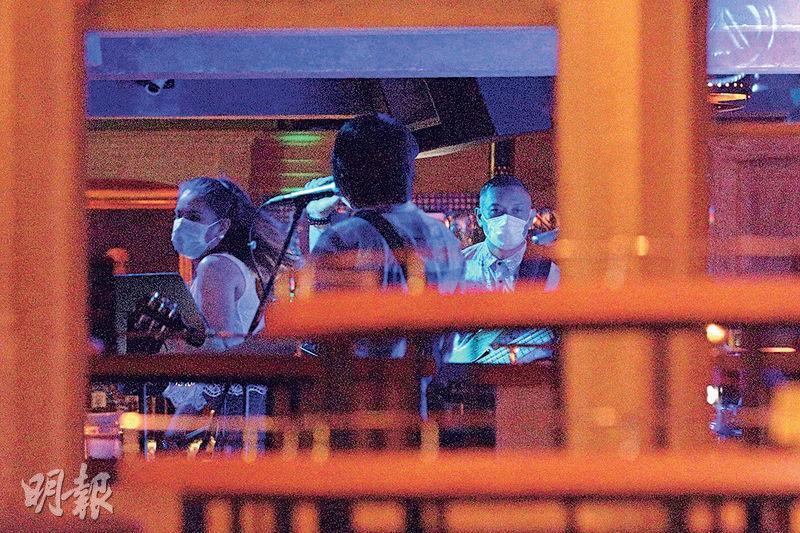 政府今日零時起放寬酒吧防疫措施,容許現場表演,曾爆疫的蘭桂坊酒吧Insomnia,今日凌晨再現久違了的樂隊,樂隊成員都遵守規定,戴上口罩表演。(曾憲宗攝)