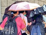 被告楊博文(白衫)昨准保釋,於支持者撑傘遮掩下離開。(戴晴曦攝)