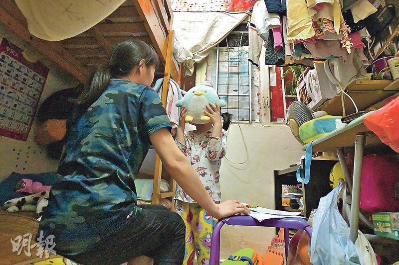 阿珍(左)與丈夫及5歲女兒(右)住在約90呎劏房,月租3600元,靠綜援應付,患腦瘤的丈夫常以無錢為由不求醫,全家每日只吃兩餐。(黃志東攝)