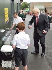 英國首相約翰遜周五到赫特福德郡探訪一間小學。(法新社)