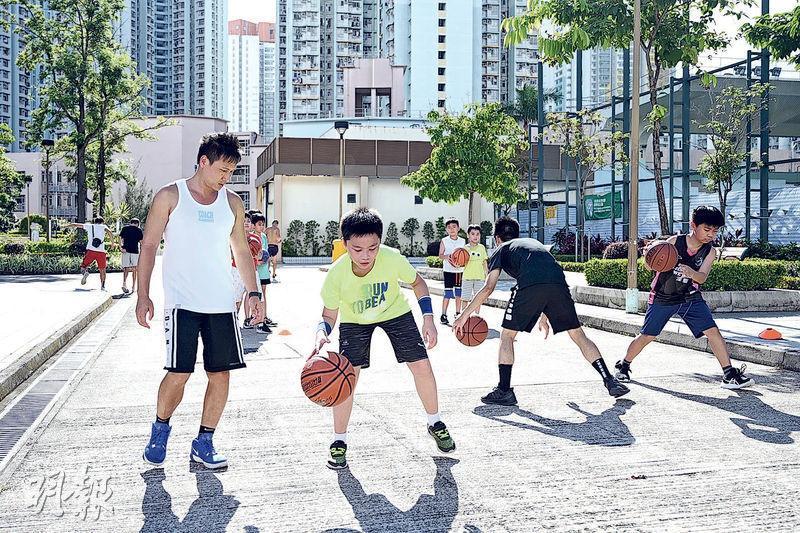 康文署球場昨重開,不少球場都聚滿波友,昨原計劃在石硤尾公園籃球場教班的香港體育教練工會籌委劉嘉豪(左一),只能改為在球場外空地開班教學。讀小六的梁同學(熒光衣)說,早前疫情期間沒運動,在家吃零食和飲汽水,體重增加不少。(賴俊傑攝)
