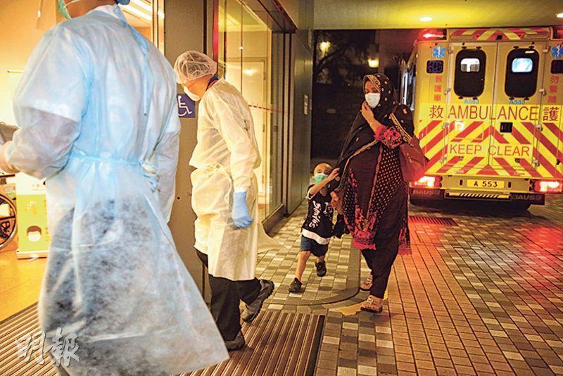 本港昨新增約30宗初步確診新冠肺炎輸入個案。一名外籍女子與小童昨晚於駿洋邨檢疫中心,由救護車送往威爾斯親王醫院治理。(伍浦鋒攝)
