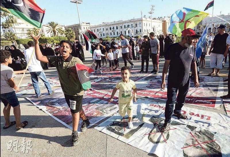 周日在利比亞民族團結政府控制的首都的黎波里,支持軍閥哈夫塔爾的法國總統馬克龍、埃及總統塞西、阿聯酋阿布扎比王儲穆罕默德的肖像被放在地上供示威者踐踏。(法新社)