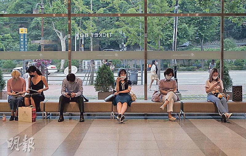 在新冠疫情下,韓國民眾上周四在首爾一間劇院等候入場觀看《歌聲魅影》。(路透社)