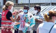 在德國費爾(Verl)的防疫隔離區,一名政府人員昨日隔着圍欄與居民傾談。(法新社)